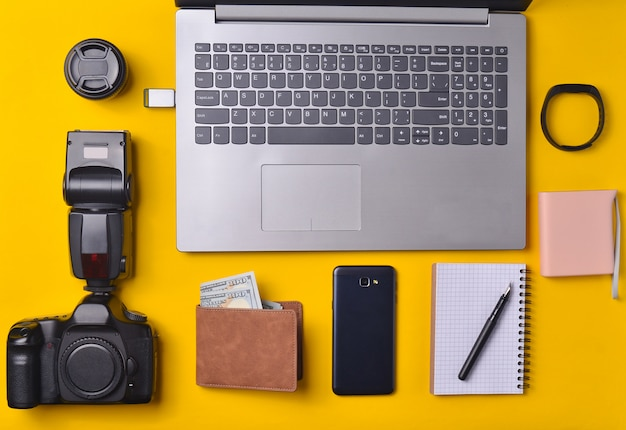 Fotografo di attrezzature, laptop, borsa con dollari, smartphone, smart watch, power bank, su uno sfondo giallo. concetto freelance, gadget per lavoro, oggetti, vista dall'alto, distesi Foto Premium
