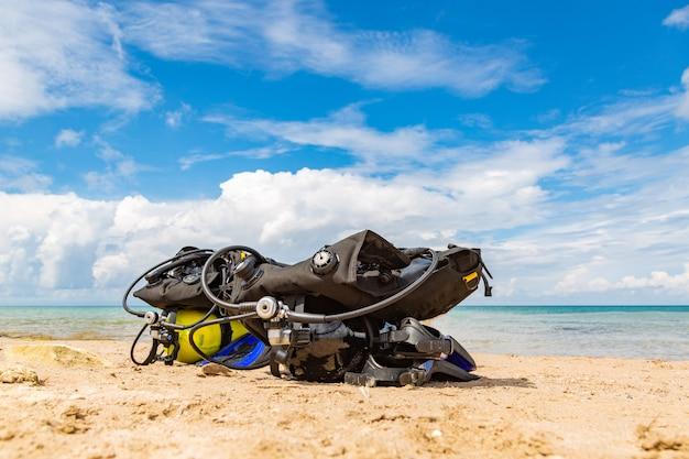 L'attrezzatura di un sub, un pallone ad ossigeno si trova sulla spiaggia. immersioni subacquee, attrezzatura, pinne, palloncini, maschere Foto Premium