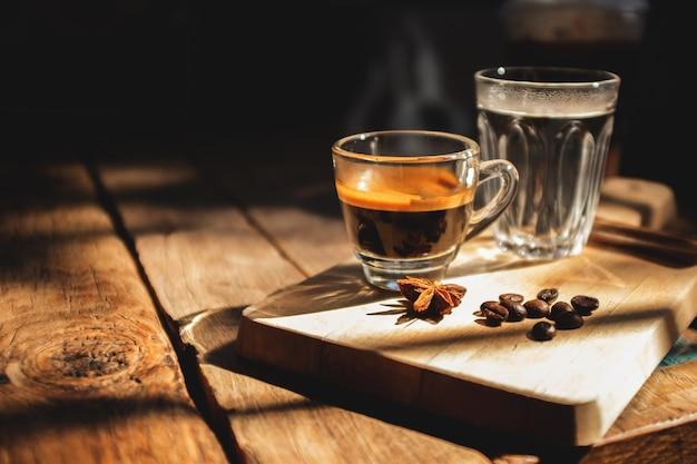 Caffè espresso e acqua fredda su un vecchio tavolo di legno. Foto Premium