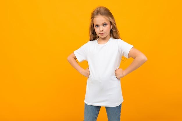 Ragazza carina europea in una maglietta bianca con un modello su un muro giallo Foto Premium