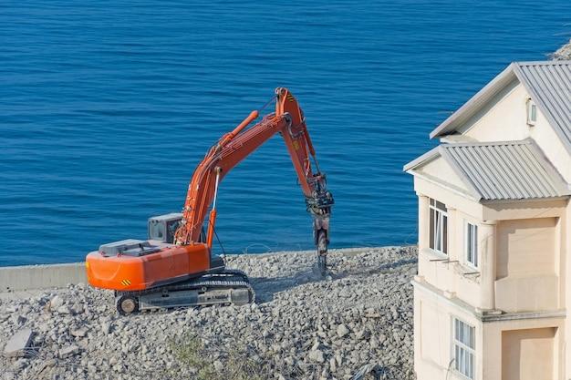 Escavatore con cesoia idraulica contro un edificio demolito. smantellamento della costruzione di emergenza in piedi in riva al mare. Foto Premium