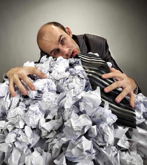 Uomo d'affari depressivo esaurito che pone sui documenti sgualciti Foto Premium