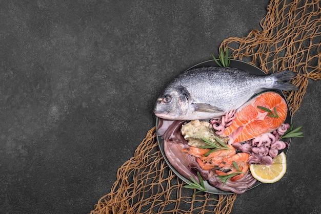 Piatto di frutti di mare esotici in un piatto e rete da pesca Foto Premium