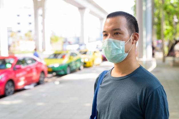 Volto di giovane asiatico con maschera per protezione dall'epidemia di coronavirus alla stazione dei taxi della città Foto Premium