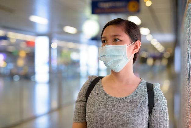 Volto di giovane donna asiatica che indossa una maschera per proteggersi dall'epidemia di coronavirus alla stazione della metropolitana Foto Premium