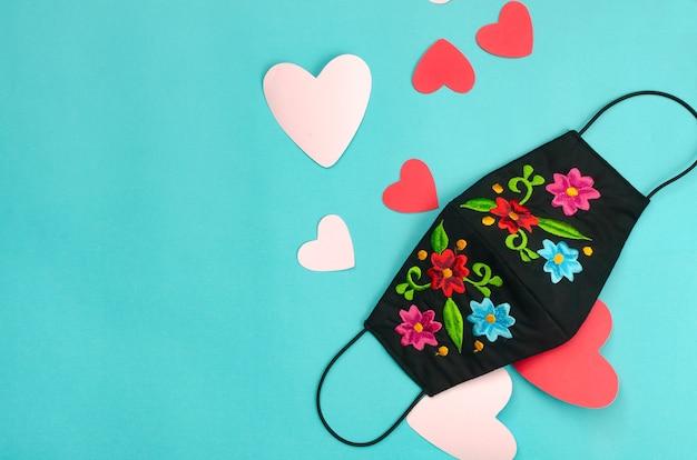 Maschera facciale decorata con fiori su sfondo blu con cuori. sfondo per san valentino. Foto Premium