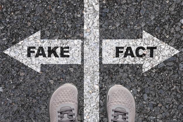 Schermata di stampa dei fatti sul segno bianco della freccia destra sulla strada e di fronte è la schermata di stampa falsa freccia bianca sinistra. Foto Premium