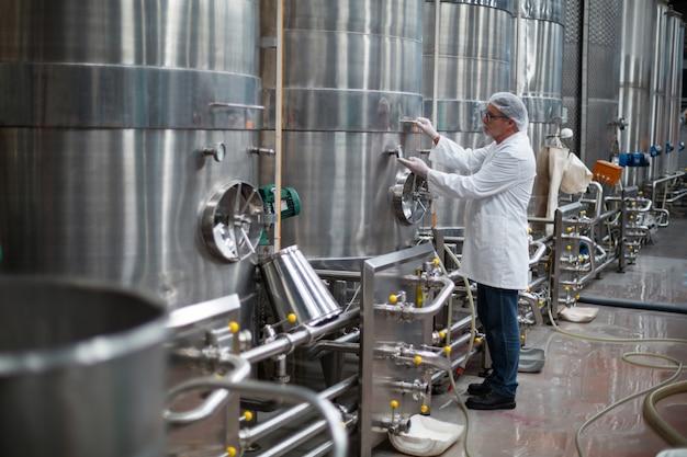 Ingegnere di fabbrica che controlla un manometro del serbatoio Foto Premium