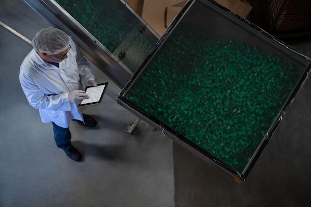 Ingegnere di fabbrica che utilizza compressa digitale nella fabbrica Foto Premium