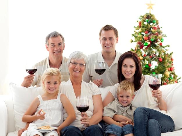Famiglia che beve vino e mangia i dolci a natale Foto Premium