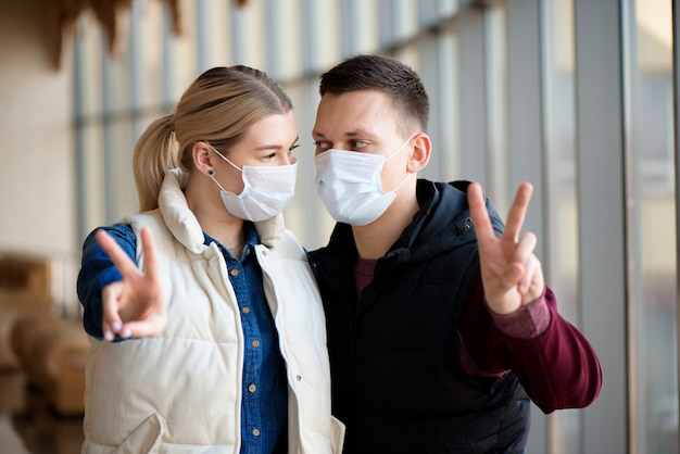Famiglia in maschera nel centro commerciale o in aeroporto. la coppia indossa una maschera facciale durante il coronavirus e l'epidemia di influenza. protezione da virus e malattie in luoghi pubblici affollati. Foto Premium