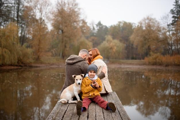 Famiglia che si rilassa all'interno e che segna il cane di animale domestico Foto Premium