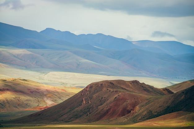 Fantasia vasto paesaggio con vivaci montagne multicolori alla luce del sole. Foto Premium