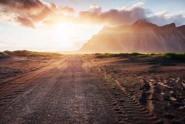 Fantastico tramonto sulle montagne e vulcaniche dune di sabbia lavica sulla spiaggia di stokksness. una giornata calda e un deserto Foto Premium