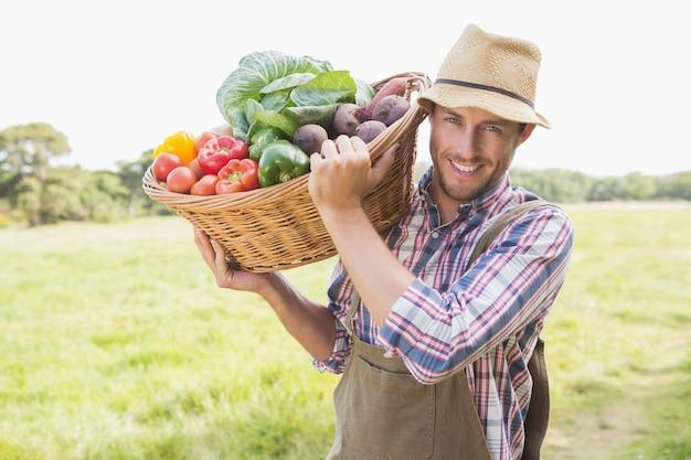 Agricoltore che trasporta cesto di verdura Foto Premium