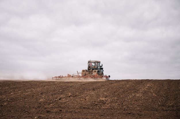 Contadino in trattore preparazione terreno con coltivatore letto di semina in terreni agricoli. il trattore ara un campo. lavori agricoli in lavorazione, coltivazione della terra. agricoltori che preparano la terra e concimano. agricolo Foto Premium