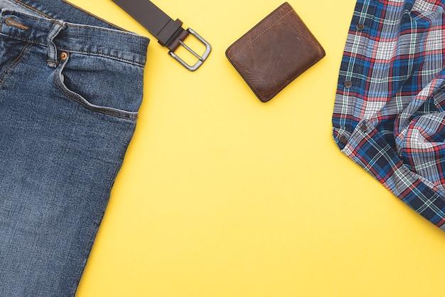 Sfondo di moda, jeans, camicia, cintura, portafoglio. stile denim. vista dall'alto. abiti da uomo su sfondo giallo, spazio per il testo. Foto Premium