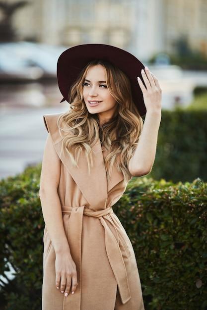 Ragazza alla moda bella e sensuale modella bionda in cappotto senza maniche che adegua il suo cappello alla moda, sorridente e in posa all'aperto presso la strada della città Foto Premium