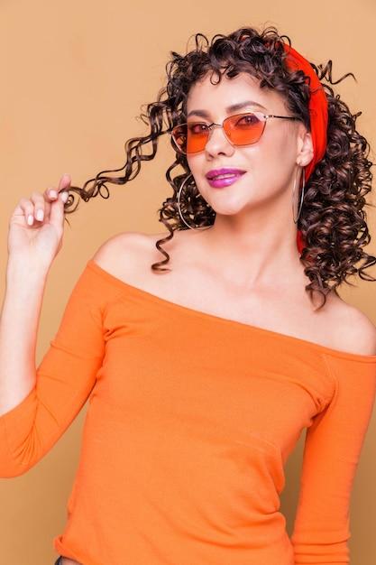 Ragazza bruna alla moda in un maglione arancione brillante, occhiali e una bandana in posa sull'arancio Foto Premium
