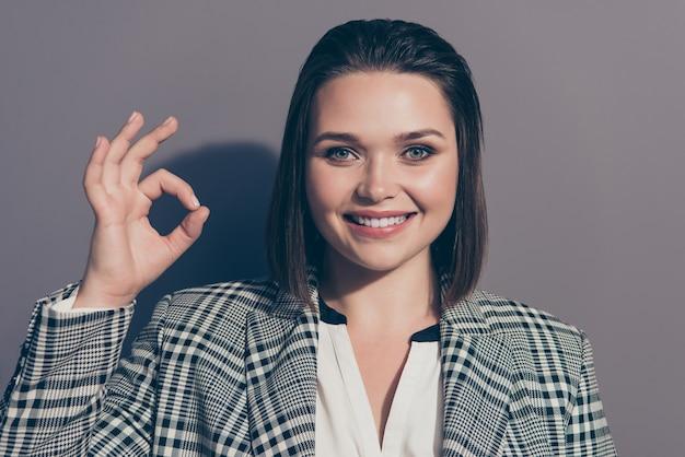 Donna di affari alla moda che indossa un blazer a scacchi in posa all'interno Foto Premium