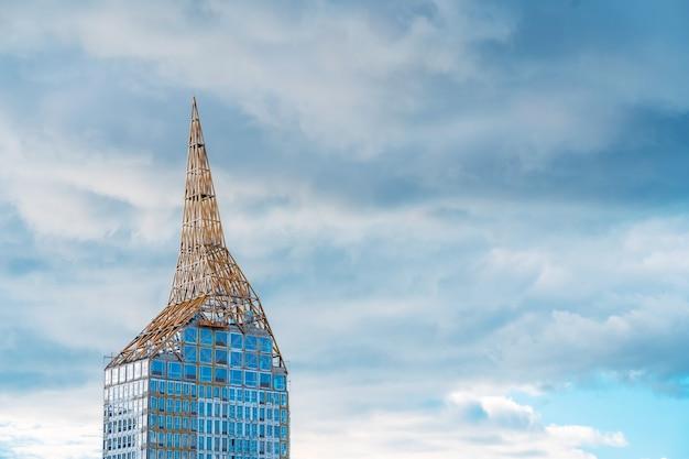 Un edificio in vetro alla moda in costruzione, guglia incompiuta con foreste Foto Premium