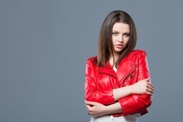 Stile alla moda, abbigliamento femminile alla moda, combinazione di colori. bella ragazza castana in vestito bianco e sfondo grigio isolato giacca di pelle rossa. Foto Premium