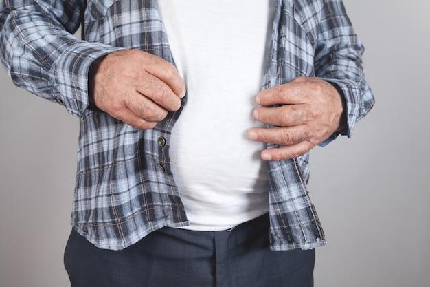 Bottoni di fissaggio uomo grasso sulla camicia a sfondo grigio dieta Foto Premium