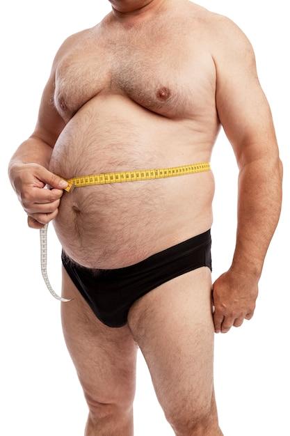 Un uomo grasso in pantaloncini misura il volume dell'addome. isolato. avvicinamento. Foto Premium