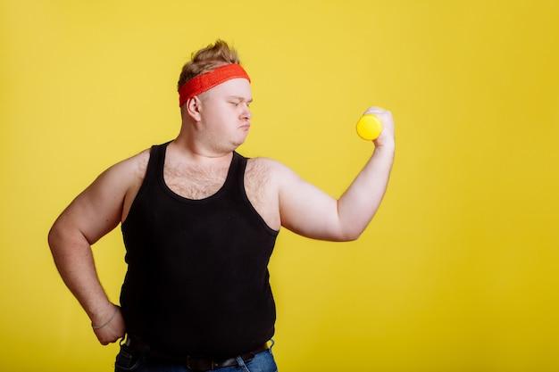 Uomo grasso con manubri sulla parete gialla. motivazione per le persone grasse Foto Premium