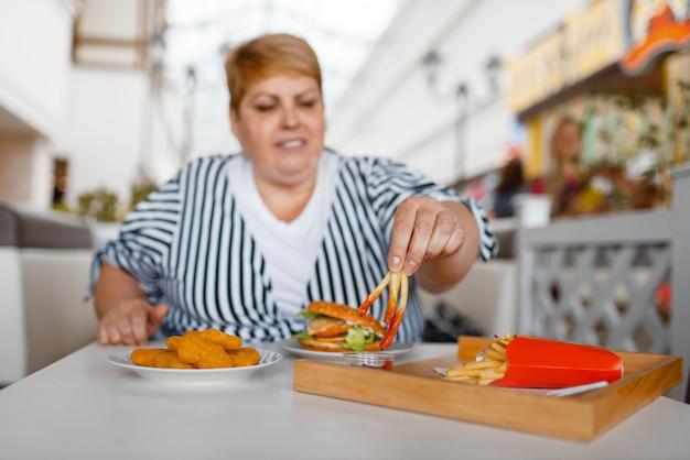 Donna grassa che mangia patatine fritte nella food court del centro commerciale. persona di sesso femminile in sovrappeso al tavolo con pranzo spazzatura, problema di obesità Foto Premium