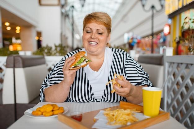 Donna grassa che mangia cibo ad alto contenuto calorico nel ristorante fastfood. persona di sesso femminile in sovrappeso al tavolo con cena spazzatura, problema di obesità Foto Premium