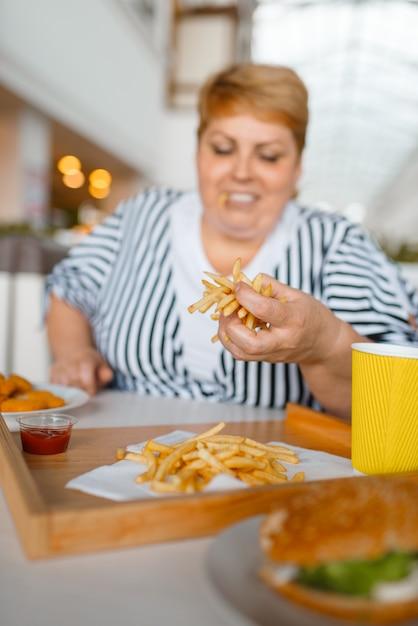 Donna grassa che mangia cibo ad alto contenuto calorico nel centro commerciale Foto Premium