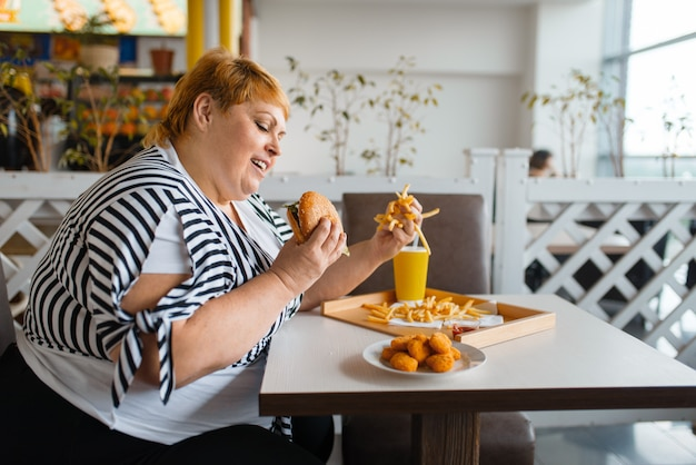 Donna grassa che mangia cibo ipercalorico nel ristorante Foto Premium
