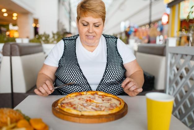 Donna grassa che mangia pizza in un ristorante fastfood. persona di sesso femminile in sovrappeso al tavolo con cena spazzatura, problema di obesità Foto Premium