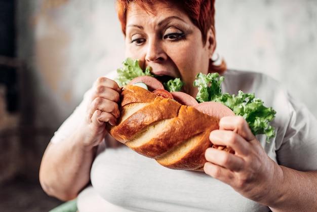 La donna grassa mangia panino, sovrappeso e bulimica. stile di vita malsano, obesità Foto Premium