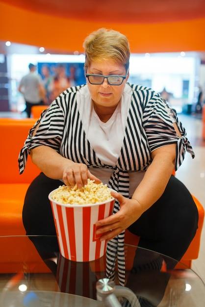 Donna grassa che tiene popcorn nella sala del cinema Foto Premium