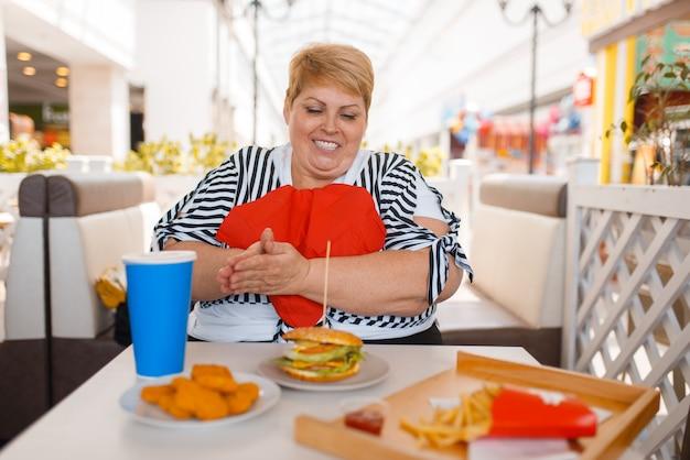 La donna grassa si prepara a mangiare un fast food nella food court del centro commerciale. persona di sesso femminile in sovrappeso al tavolo con pranzo spazzatura Foto Premium
