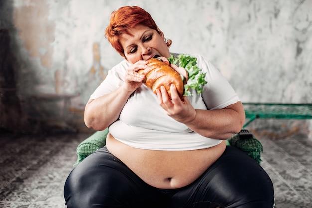 La donna grassa si siede sulla sedia e mangia il panino, bulimico Foto Premium