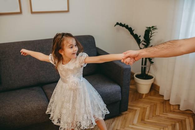 Padre che balla con la sua piccola figlia vestita di bianco mentre si diverte in salotto Foto Premium