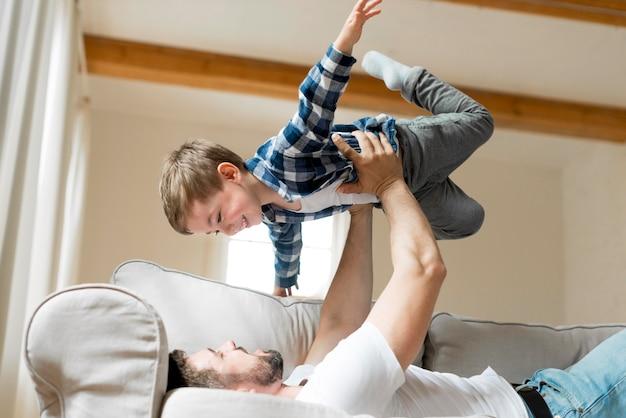 Padre che tiene suo figlio in aria Foto Premium