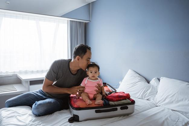 Padre seduto tenendo e baciando un bambino che era seduto in una valigia aperta Foto Premium