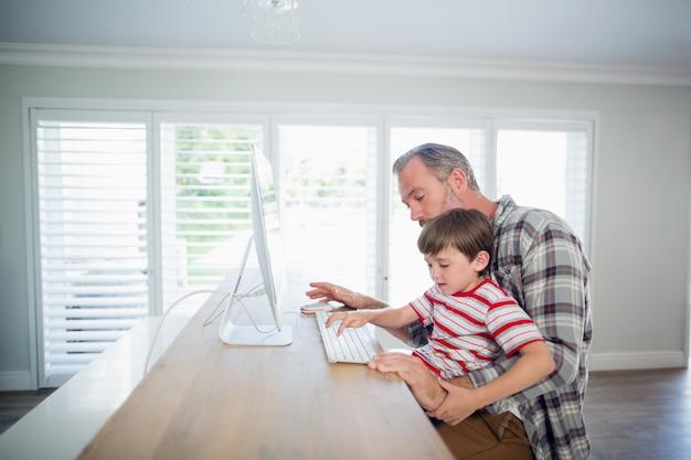 Padre e figlio che lavorano al computer Foto Premium