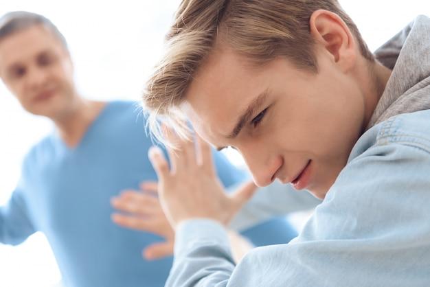Padre oscilla la mano per colpire il suo adolescente tormentato Foto Premium