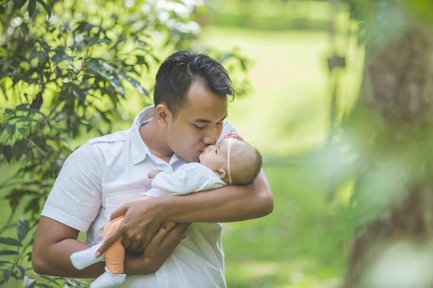 Padre con il suo bambino appena nato nel parco. Foto Premium