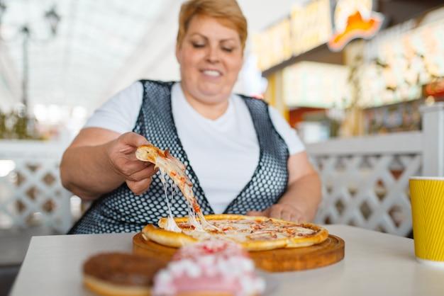 Donna grassa che mangia pizza in un ristorante fastfood, cibo malsano. persona di sesso femminile in sovrappeso al tavolo con cena spazzatura, problema di obesità Foto Premium