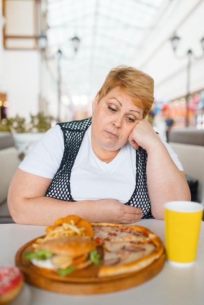 Donna grassa che mangia pizza nel ristorante fastfood Foto Premium