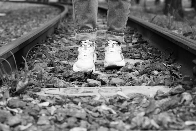 Piedi in scarpe da ginnastica sui binari della ferrovia Foto Premium