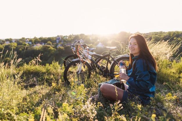 Femmina dopo aver guidato la bici seduto sul prato Foto Premium