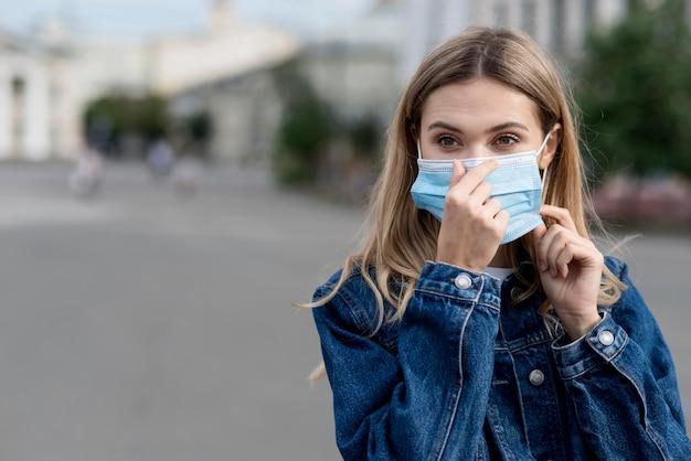 Femmina che organizza la sua maschera medica per protezione Foto Premium