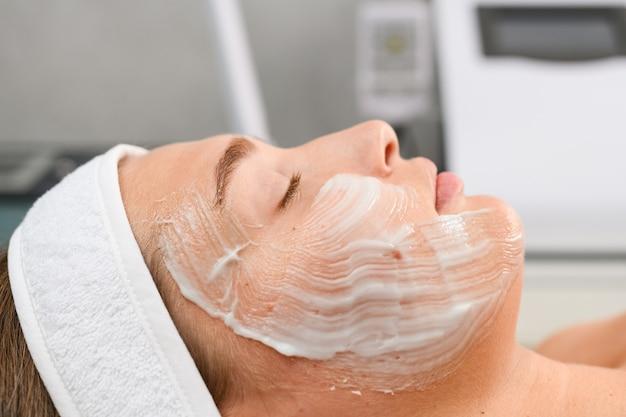 Il cliente femminile si rilassa con gli occhi chiusi giaceva sul divano al salone di bellezza spa Foto Premium